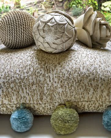 Olivia Bard -  Tamed Spirit Fabric Collection - Close view of a luxurious cushion in beige featuring elegant gold decorations and colourful pompoms on edges