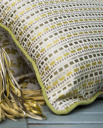 Olivia Bard -  Tamed Spirit Fabric Collection - White cushion with lime green edges decorated with a pattern of silver and gold squares and thin stripes