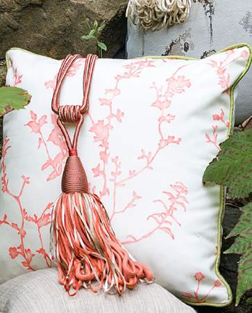 Olivia Bard -  Tamed Spirit Fabric Collection - White cushion with coral red edges and branch pattern in the same colour with coral red curtain tie back