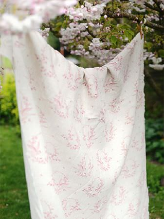 Peony and Sage -  Birdsong and Co Fabric Collection - Floral patterned fabric made in white and light pink, hanging over a washing line in a garden