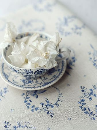 Peony and Sage -  Birdsong and Co Fabric Collection - White petals scattered in a navy and white patterned teacup and saucer, sitting on blue and very pale grey floral fabric