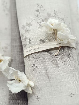 Peony and Sage -  Birdsong and Co Fabric Collection - A scroll of bird and floral patterned fabric tied with white ribbon, scattered with a white flower and petals