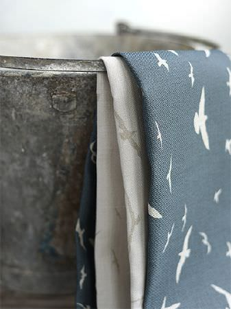 Peony and Sage -  Coastal Fabric Collection - Bird print fabrics, one in white and grey, one in white and blue, draped over a dark silver coloured bucket