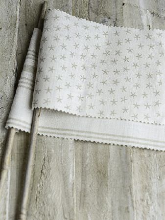 Peony and Sage -  Coastal Fabric Collection - Wooden boards beneath small flags made from sticks and white and grey patterned fabrics with stripes and stars