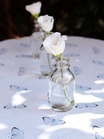 Peony and Sage -  Coastal Fabric Collection - White and pale blue butterfly print fabric on a table with three clear glass bottles, each holding a single white flower