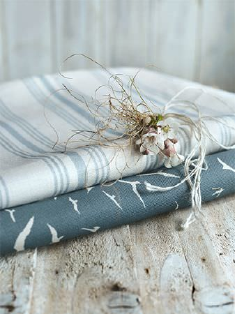 Peony and Sage -  Coastal Fabric Collection - Grey and white striped fabric over a fold of blue and white bird print fabric, with white twigs on a rustic wooden bench