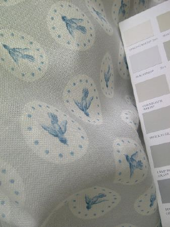 Peony and Sage -  Coastal Fabric Collection - Small pieces of fabric in various grey shades, beside a large light grey piece of fabric with white circles and blue birds