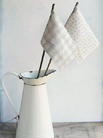 Peony and Sage -  Coastal Fabric Collection - White ceramic jug holding flags with two sticks tied to swatches of grey-beige and white checked and star print fabrics