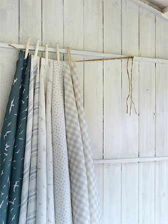 Peony and Sage -  Coastal Fabric Collection - Checked, striped and patterned fabrics in white, dark blue and grey-beige pegged on a piece of string with wooden boards