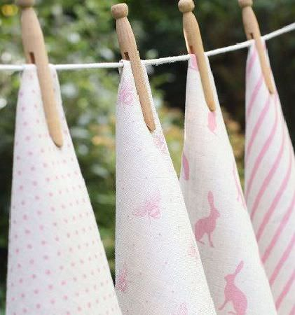 Peony and Sage -  Country Life Fabric Collection - Four pieces of pink and white fabric pegged onto a washing line, featuring dots, stripes, hares and bee prints