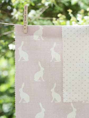Peony and Sage -  Country Life Fabric Collection - Pale pink-grey and white polka dots and hare silhouettes on pieces of fabric held onto a washing line by a wooden peg