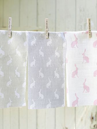 Peony and Sage -  Country Life Fabric Collection - Grey and white, blue and white, and pink and white hare silhouette print fabrics held onto string with three wooden pegs