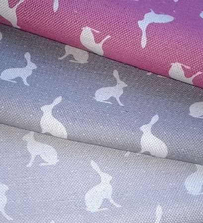 Peony and Sage -  Country Life Fabric Collection - Three folds of fabric with white hares, onewith a light grey background, one in dark grey, and one made in dark pink