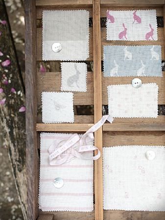 Peony and Sage -  Country Life Fabric Collection - Wooden box frame with small white samplesof plain, patterned and hare print fabrics, withbuttons and ribbon