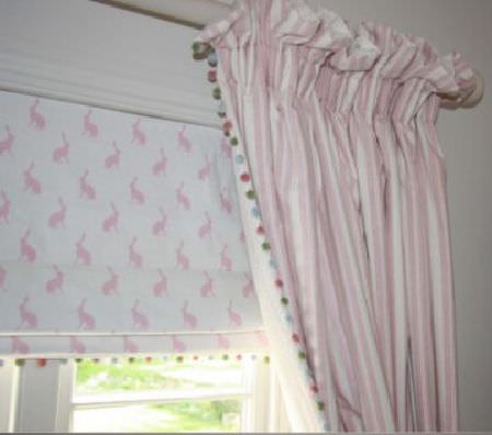 Peony and Sage -  Country Life Fabric Collection - Pink and white striped curtains edged with multicoloured pompoms, with a pompom-edged pink and white hare print roller blind