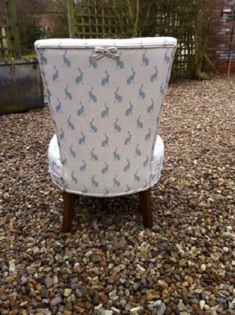 Peony and Sage -  Country Life Fabric Collection - Back view of an armchair covered in white fabric with a light blue hare print, with a small bow and dark wooden legs