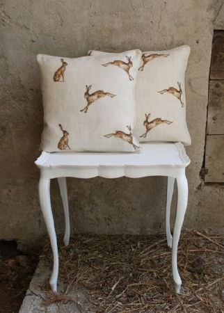 Peony and Sage -  Country Life Fabric Collection - Two square cushions made with brown and off-white hare print fabric, on a small, decorative plain white occasional table