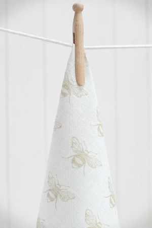 Peony and Sage -  Country Life Fabric Collection - String with a wooden peg holding a swathe of white fabric featuring a simple, repeated light grey-beige bee design
