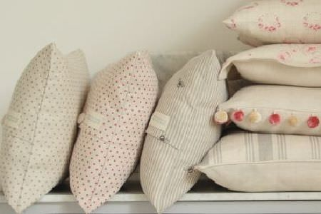 Peony and Sage -  Country Life Fabric Collection - Stacks of dotted, striped, plain, floral patterned and pompom-edged cushions made in shades ofoff-white, grey and pink