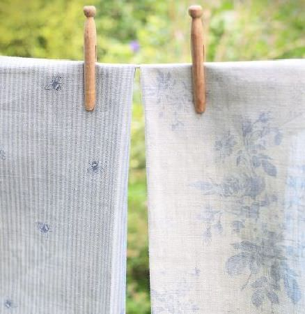 Peony and Sage -  Country Life Fabric Collection - Pale blue and white floral fabric beside blue and white stripe and bee print fabric held onto string with two wooden pegs