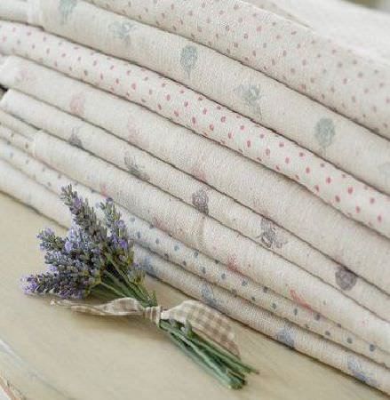 Peony and Sage -  Country Life Fabric Collection - A bouquet of lavender beside a stack of fabrics featuring grey, blue, pink and off-white polka dots, bees and florals