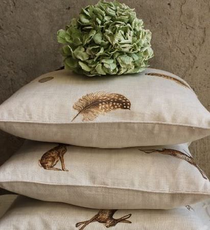 Peony and Sage -  Country Life Fabric Collection - A stack of 3 off-white cushions with hare and feather prints in shades of brown, topped with a large round leafy object