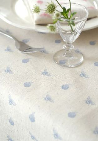 Peony and Sage -  Country Life Fabric Collection - Blue bees and beehives printed on white fabric beneath a fork, a plate and a glass holding a small flower