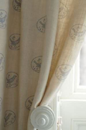 Peony and Sage -  Country Life Fabric Collection - A large white circular curtain holder holding off-white coloured curtains patterned with light blue-grey ovals and birds