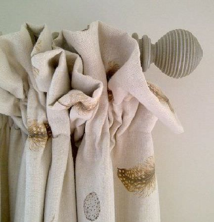 Peony and Sage -  Country Life Fabric Collection - Light grey curtain pole holding a curtain made from off-white fabric with feather patterns in shades of brown and grey