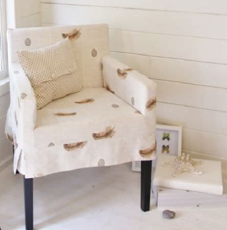 Peony and Sage -  Country Life Fabric Collection - Tall armchair with wooden legs covered with a cream and brown feather print fabric with a knitted cushion and a starfish