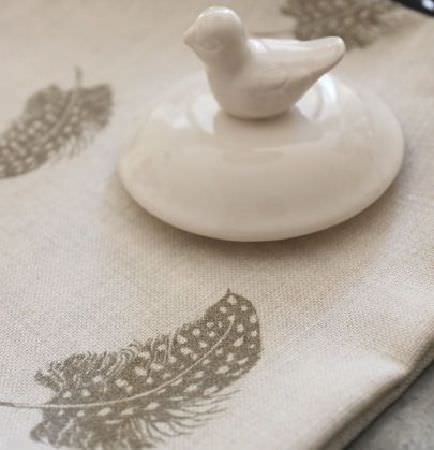Peony and Sage -  Country Life Fabric Collection - Off-white fabric printed with realistic light grey feathers, placed beneath a cream coloured ceramic bird-topped lid