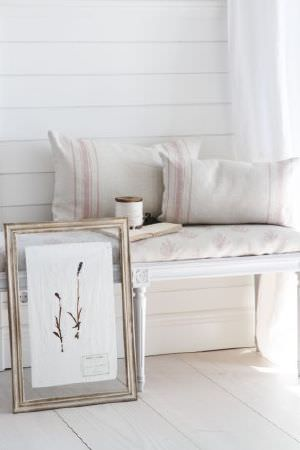 Peony and Sage -  Finca Fabric Collection - A framed picture beside a white bench with subtly patterned and striped seat and scatter cushions in pale shades of pink