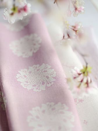 Peony and Sage -  Finca Fabric Collection - Small, pretty white and pink flowers beside a fold of light baby pink coloured fabric featuring a white floral pattern