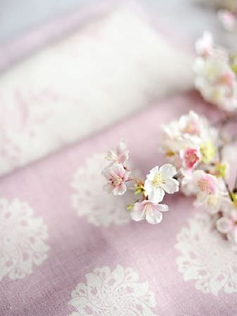 Peony and Sage -  Finca Fabric Collection - Pale pink fabric with white florals, on a fold of white fabric with pink florals, placed with small pink and white flowers