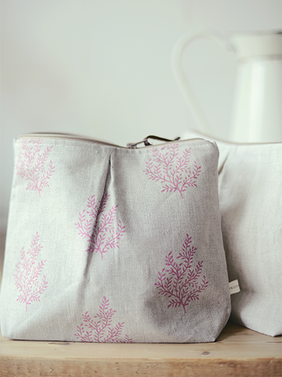 Peony and Sage -  Finca Fabric Collection - A table with a white jug and two bagsmade with plain white fabric, and subtle leaf patterned light pink and grey fabric