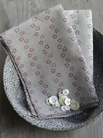 Peony and Sage -  Finca Fabric Collection - A dark grey and white basket filled with buttons and two grey fabrics featuring small, stylised dark pink and grey flowers