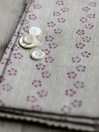 Peony and Sage -  Finca Fabric Collection - Six cream coloured buttons scattered on a fold of floral fabric with a small stylised design in dark pink and cement grey