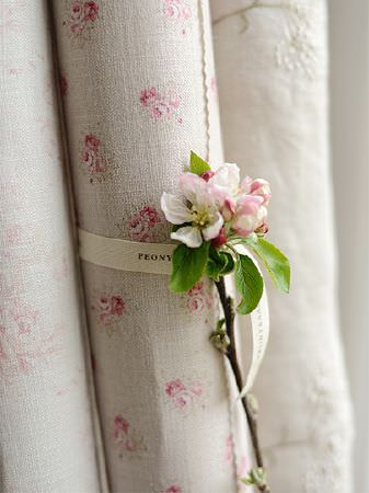 Peony and Sage -  French Florals Fabric Collection - A pink flower placed on a scroll of pink andcream floral fabric tied with a ribbon, beside off-white embroidered fabric