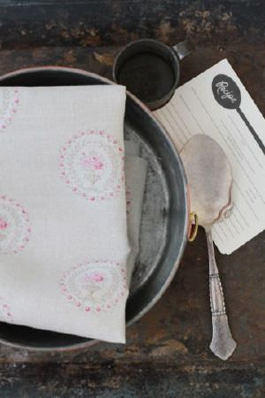 Peony and Sage -  French Florals Fabric Collection - A dark table with a metal mug and bowl, a recipe card, a spoon, and folded off-white fabric with a circular floral design