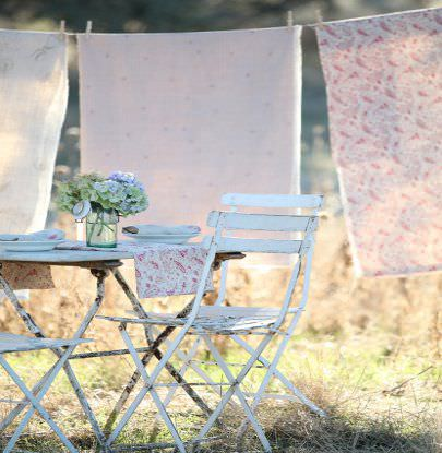 Peony and Sage -  French Florals Fabric Collection - 3 white and pink fabrics with different patterns, hanging from a washing line beside a rustic white outdoor table and chairs