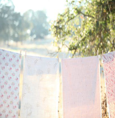 Peony and Sage -  French Florals Fabric Collection - Four different white and light pink floral and patterned fabrics hanging over an outdoor washing line