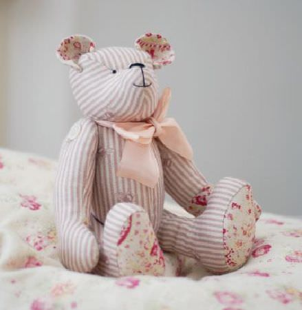 Peony and Sage -  French Florals Fabric Collection - A nude ribbon around a stuffed teddy bear made from fabrics with beige and white stripes and pink and white florals