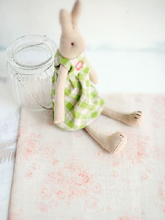 Peony and Sage -  French Florals Fabric Collection - A beige stuffed bunny wearing a bright green checked dress, sitting against a glass jar on subtly patterned cream fabric