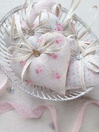 Peony and Sage -  French Florals Fabric Collection - Padded hearts made withfloral, striped and dotted fabrics in light grey, pink and blue, with grey ribbon, ina white bowl