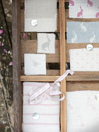 Peony and Sage -  French Florals Fabric Collection - A wooden crate with swatches ofbunny, bee, stripe, dot and floral fabrics in off-white and pale blue, grey and pink shades