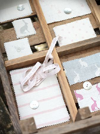 Peony and Sage -  French Florals Fabric Collection - Ribbon, buttons and swatches of pale coloured bunny, bee, floral, dotted and striped fabrics placed in a wooden crate