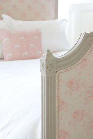 Peony and Sage -  French Florals Fabric Collection - A bed with a wooden frame, white bedding, a subtle floral patterned headboard and footboard,and a pink and white cushion