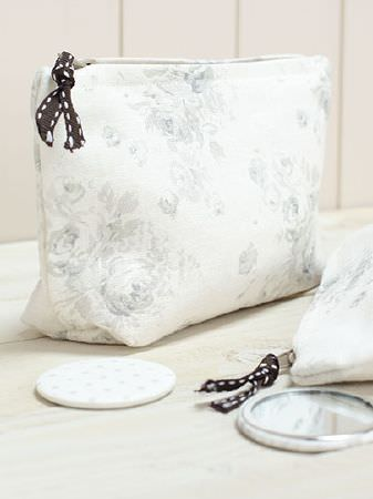 Peony and Sage -  French Florals Fabric Collection - A white compact mirror with black ribbon tied on two fabric bags made with subtle floral patterns in pale grey and white