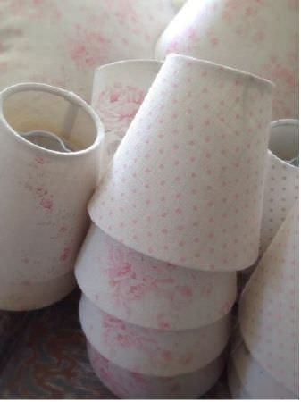 Peony and Sage -  French Florals Fabric Collection - Stacks of lampshades, all covered with fabrics featuring subtle florals or polka dots inoff-white and pale pink shades