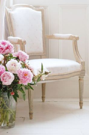 Peony and Sage -  French Florals Fabric Collection - Pink flowers in a glass vase, beside a wooden framed armchair made with a bright white padded seat and back